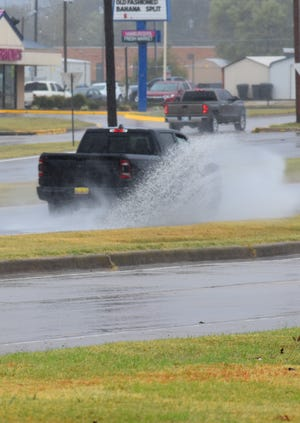 A vehicle splashes through standing water on South Commerce Street on Monday.