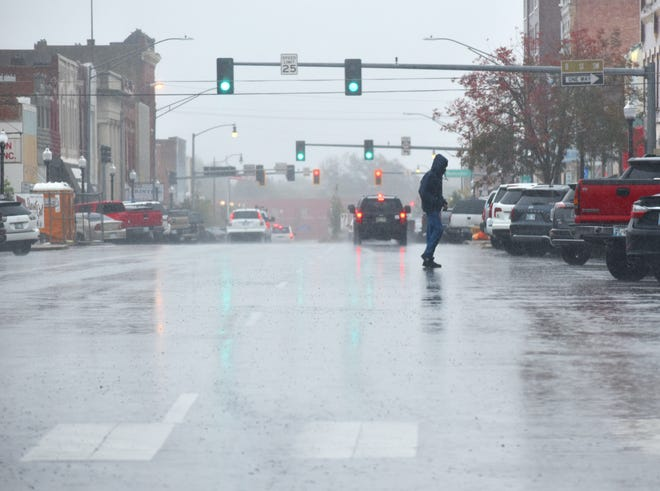 A person walks across West Main Street on a rainy Monday afternoon.
