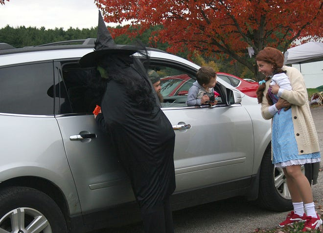 Aaron Sager Jr., 3, leans out the window while being greeted by representatives of Ashland County Council on Aging dressed as Wizard of Oz characters during The Ashland County Historical Society  Pumpkin Glow. (Playing Dorothy is executive director Sandy Enderby.) The event was Saturday, Oct. 24, 2020 at the former Children's Home on Center Street. Due to Covid-19 restrictions, the event was a drive-through event. Visitors drove through the grounds to view Halloween decorations and decorated booths from local businesses.  Visitors also viewed jack-o-lanterns, performances by Ashland University cheerleaders, and received trick-or-treat bags and giveaways. Ashland Mayor Matt Miller was among those giving away candy at the event. LIZ A. HOSFELD/FOR TIMES-GAZETTE