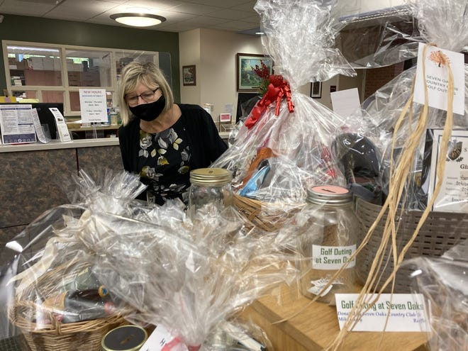 Diane Wakefield, director of Beaver Area Memorial Library, looks at some of the approximately  30 baskets donated for the library's annual fall festival.