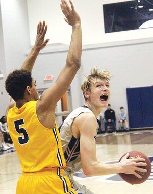 Oklahoma Wesleyan University's Kaleb Stokes, right, attacks the basket during men's basketball action last season. Stokes was the team's second-leading scorer.