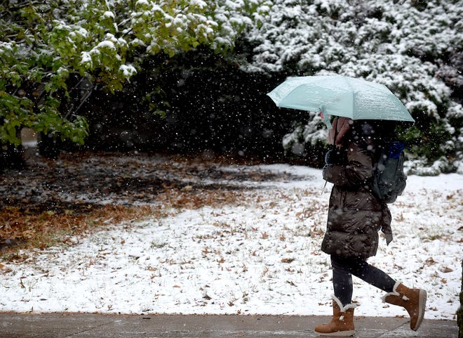 A University of Missouri student walks on Ninth Street during light snow on Monday to Middlebush Hall. The National Weather Service is forecasting cold and chilly weather with a chance of rain on Tuesday.