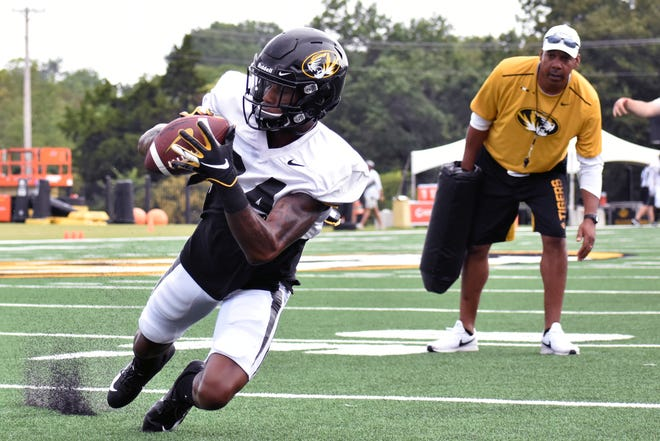 Missouri wide receiver Maurice Massey (84) dives to catch a pass while former Tigers' wide receivers coach Garrick McGee looks on during a team practice on Aug. 7, 2019 at the Kadlec Practice Fields.