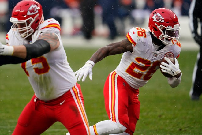 Kansas City Chiefs running back Le'Veon Bell, right, runs with the ball during the second half against the Denver Broncos Sunday in Denver.