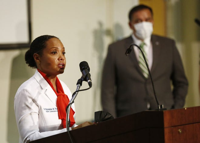 Columbus Mayor Andrew J. Ginther, right, listens as Columbus Public Health Commissioner Dr. Mysheika Roberts talks about the recent increase in COVID-19 cases during a news conference Monday.