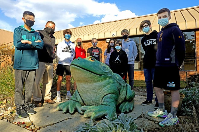 Shawn Kaeser and a group of his social-studies students pose with the bullfrog statue at Grizzell Middle School in Dublin. Kaeser's students have been involved in getting two bills passed in the past 10 years: one naming the bullfrog named as Ohio's official state frog, and another, signed last week by Gov. Mike DeWine, creating a bullfrog license plate.
