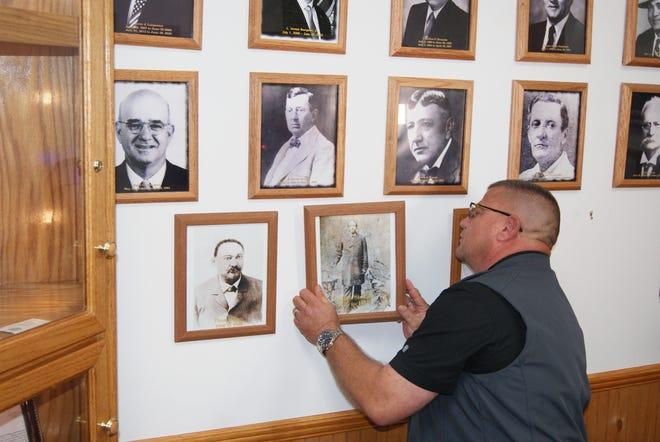 Sheriff Tim Soignet hangs the photo of Former Sheriff Jordan Stewart who served Terrebonne Parish from 1876 to 1878.