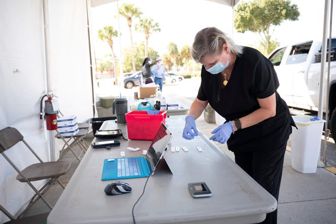 A health care worker conducts a rapid test for COVID-19 last month at the Lake Square Mall. [Cindy Peterson/Correspondent]