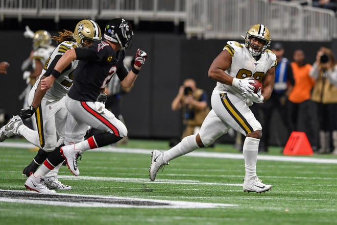 New Orleans Saints defensive tackle Shy Tuttle (99) runs after intercepting a pass thrown by Atlanta Falcons quarterback Matt Ryan (2) (left) during the second half at Mercedes-Benz Stadium on Nov. 28, 2019.