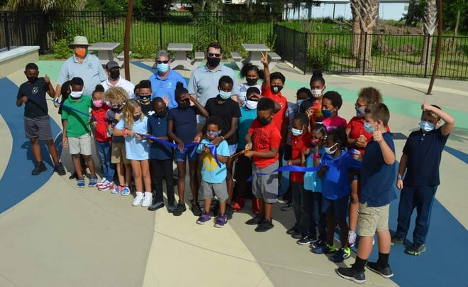 """Children in the Alonzo """"Babe"""" James Community Center's after-school program cut the ribbon on the city's first splash pad, which opened to the public Friday as City Commissioners Michael Kolody, Jason McGuirk, Randy Hartman and Mayor Russ Owen look on. The park, located at 201 Myrtle Ave., is free to visit and open from 8 a.m. to 7 p.m."""