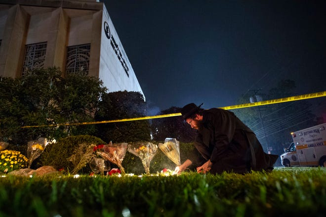 Rabbi Eli Wilansky lights a candle after a mass shooting at Tree of Life Synagogue in Pittsburgh's Squirrel Hill neighborhood. The three congregations sharing space at the Tree of Life synagogue relocated after an anti-Semitic gunman killed 11 worshippers. In March 2020, the congregations dispersed from their new locations due to the coronavirus pandemic and switched to virtual services.