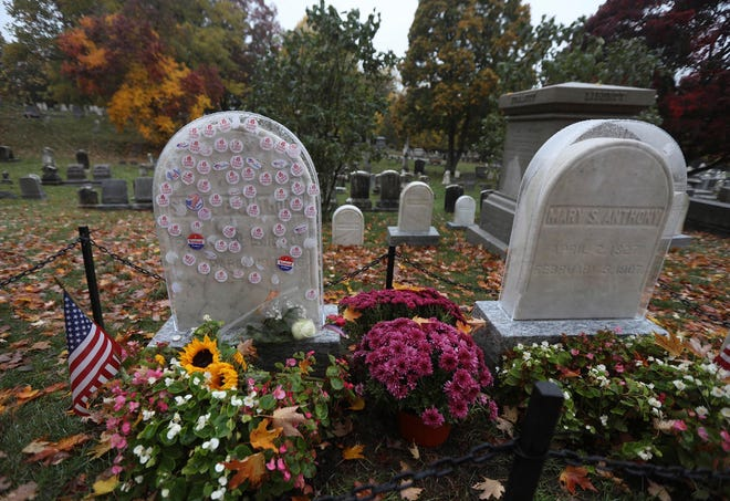 """I Voted Today"" stickers decorate a protective plastic cover on the headstone, left, of Susan B. Anthony in Mt. Hope Cemetery in Rochester, N.Y. The Friends of Mt. Hope placed plastic covers on the headstones of Anthony and her sister, Mary Anthony, as visitors have placed stickers on them since early voting started Oct. 24."
