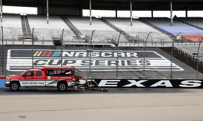 Drying trucks continue to dry the track in an attempt to get it ready for a NASCAR Cup Series auto race after morning rain prevented the 9 a.m. rescheduled start at Texas Motor Speedway in Fort Worth, Texas, Monday, Oct. 26, 2020. (AP Photo/Richard W. Rodriguez)