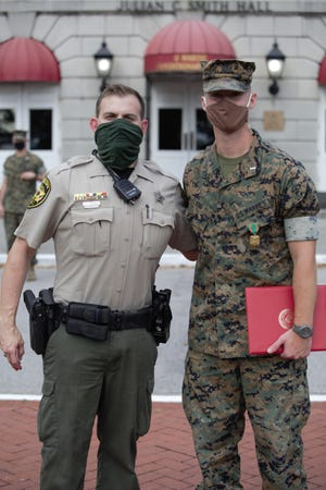 U.S. Marine Corps 1st Lt. Tyler King, a communication strategy and operations officer with II Marine Expeditionary Force, poses for a photo with Theodore Cavanagh, an Onslow County Sheriff's Office deputy officer, after an awards ceremony on Camp Lejeune, Oct. 23. King was awarded the Navy and Marine Corps Achievement Medal for acts of initiative and compassion towards a stranger.
