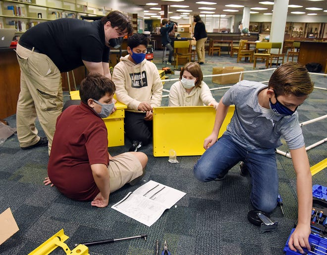 First Tech Challenge team coach John Hollar helps with the assembly of a tool chest by students, from left, Jason Jacobs of Woodington Middle School and Naylan Ramirez, Maddy White and Zachary Yarus, all of Contentnea-Savannah K-8 School. [CONTRIBUTED PHOTO]