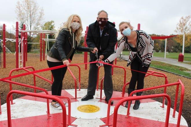 Kelly Bossell, Mayor John Pribonic and Taylore Woodard cut the ribbon opening a stand and spin at the Kid Station playground, 4200 Fishcreek Road.