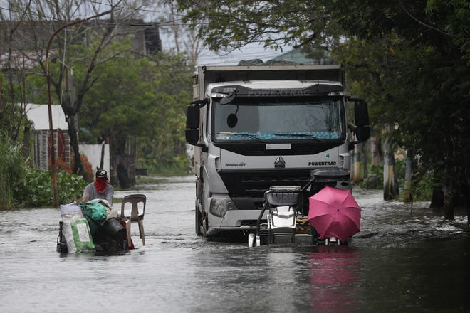 Motorists with an umbrella negotiate a flooded road due to Typhoon Molave in Pampanga province, northern Philippines, on Monday. A fast-moving typhoon forced thousands of villagers to flee to safety in provinces south of the Philippine capital Monday, flooding rural villages and ripping off roofs, officials said.