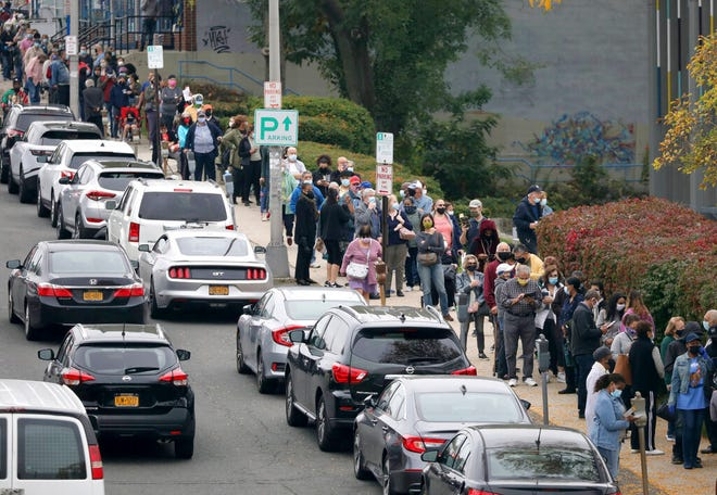 Voters line up in front of the Yonkers Public Library in Yonkers, N.Y., on Saturday, Oct. 24, 2020 as the first day of early voting in the presidential election begins across New York state.