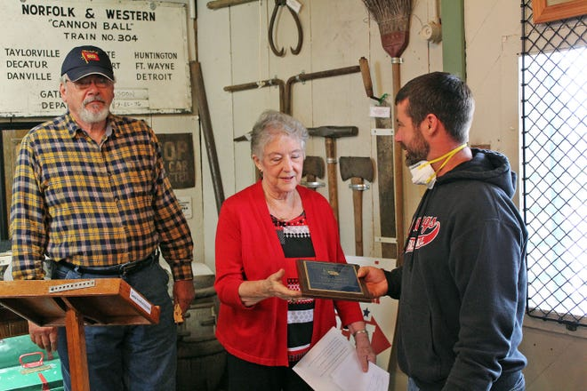 Charlie Hamilton, right, representing the family of the late Lloyd Deierling, presents the George C. Drake award Saturday to be hung at the Moberly Railroad Museum to Randolph County Historical Society President Joyce Cooper-Campbell. Deierling was to receive the award, which is the highest honor of the Wabash Railroad Historical Society, but he died earlier this year. The award initially was presented by Robert McNeill, left, president of the Wabash society, to Deierling's family.