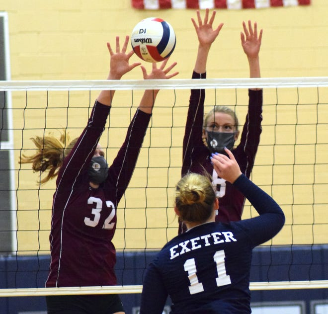 Portsmouth High School volleyball players Madelyn MacCannell (32) and Caden Merwin sport matching masks as they defend the net during a Division I match against Exeter.