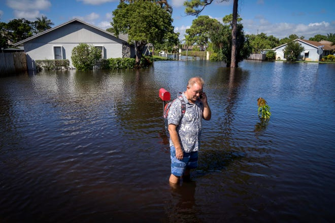Simo Volanen stands in knee-deep water after heavy weekend rain flooded the Sea Pines neighborhood in Lantana, on Oct. 26, 2020.