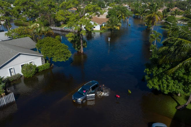 A man pushes his van out of the water after heavy rain flooded the Sea Pines neighborhood in Lantana, on October 26, 2020.