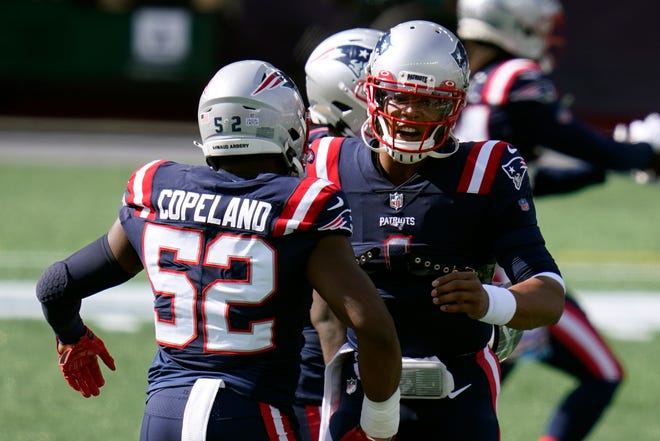 New England Patriots linebacker Brandon Copeland, left, speaks to quarterback Cam Newton, right, as the team warms up before an NFL football game against the Denver Broncos, Sunday, Oct. 18, 2020, in Foxborough, Mass. (AP Photo/Charles Krupa) ORG XMIT: NYOTK