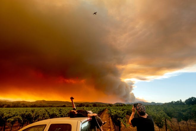 In this Thursday, Aug. 20, 2020, file photo, Thomas Henney, left, and Charles Chavira watch a plume spread over Healdsburg, Calif., as the LNU Lightning Complex fires burn. Deadly wildfires in California have burned more than 4 million acres (6,250 square miles) this year — more than double the previous record for the most land burned in a single year in the state. California fire officials said the state hit the astonishing milestone Sunday, Oct. 4, 2020 with about two months remaining in the fire season. (AP Photo/Noah Berger, File)