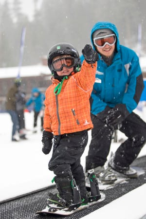 A young snowboarder and instructor move up slope on Dodge Ridge carpet lift.