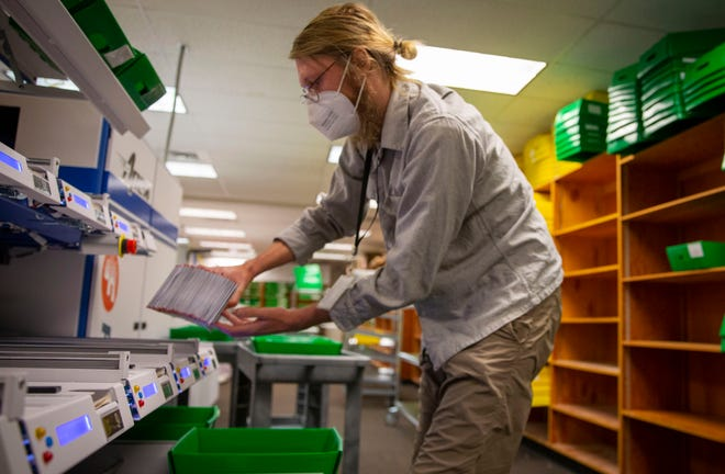 Lane County Elections worker Cooper Otte places ballot envelopes in a bin after they were scanned for signatures Monday. More than 48% of ballots have been returned by voters in Lane County.