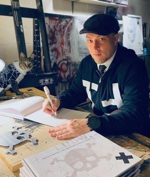 "Artist Billy Ludwig signs copies of his new book, ""Skull & Bones,"" which is a 10-year chronicle of his Thirteenth Floor studio. His cat Picasso is at left."