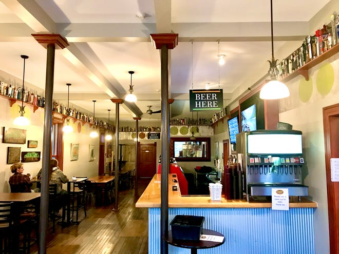 The dining room and bar at Sublime Smoke in Boliver has artwork and a beer tap collection on display, surrounding tables of different sizes and a long bartop at which patrons can study the many bottled beer options and the draft beer that's available.