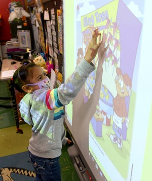 Anastasia Bowers works Monday on counting in the kindergarten class of Beth Knight at Franklin Elementary School in Massillon. Face coverings, social distancing and increased cleaning and sanitizing are now part of the school day.