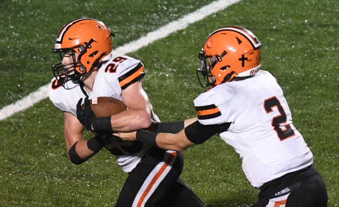 Hoover quarterback Connor Ashby (right) hands to running back Drew Robinson during the Vikings game last week at Massillon. Oct. 23, 2020.