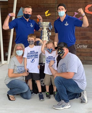 Malissa, front left, and Jesse Black, front right, with 5-year-old son Jase and 7-year-old son Mason, pose with the Stanley Cup and Tampa Bay Lightning players Steven Stamkos, top left, and Ryan McDonagh, top right, at the Children's Cancer Center in Tampa on Oct. 16. The NHL champions took the Stanley Cup to the center as part of their local tour of stops.