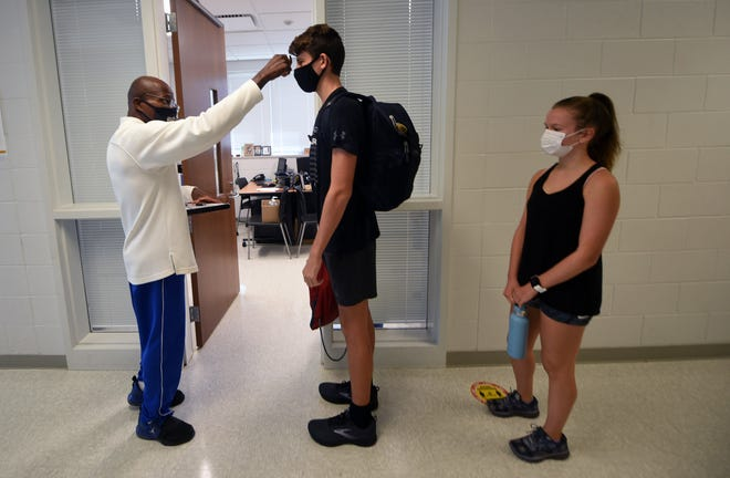 Laney cross country head coach Sam Bobbitt checks the temperature of cross country athletes prior to practice at the school in Wilmington, N.C., Monday, Oct. 26, 2020.