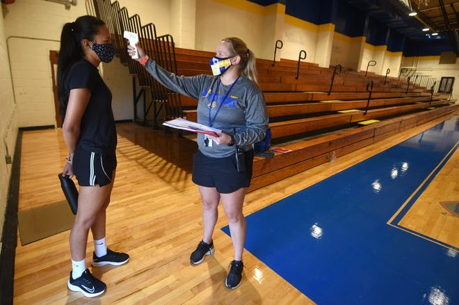 Laney head basketball coach Ashley Jones checks the temperature of Laura Holguin prior to practice at the school in Wilmington, N.C., Monday, Oct. 26, 2020. The temperature checks are a required part of the COVID-19 protocol.