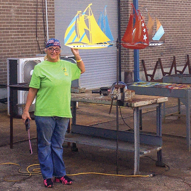 Amateur artist April Thompson shows the sailboat-themed whirligig she created at Pamlico Community College. [CONTRIBUTED PHOTO]