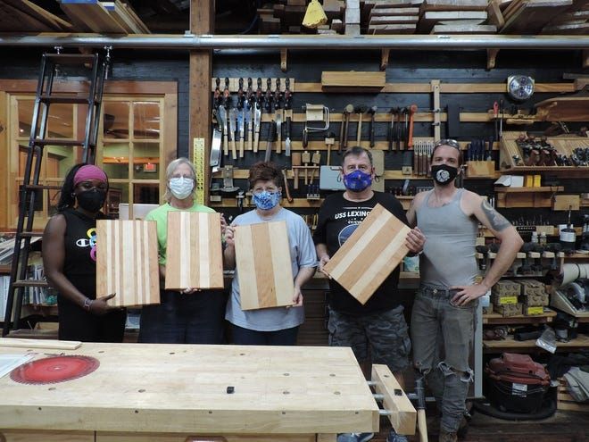 Beginning Woodworking classes have resumed at Shop Class with reduced class size and other precautions in place. Displaying their newly completed cutting boards are Rita Behrmann, Jan Willis, Nancy and Tom Corbin.  Instructor Jonathan Burger, pictured on the right, says they were all smiling under their masks. [CONTRIBUTED PHOTO]