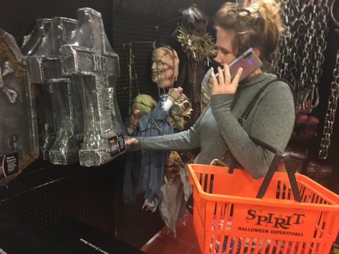 Griswold resident Alesha Causey went shopping for a decorative tombstone at Spirit Halloween in Lisbon Monday.