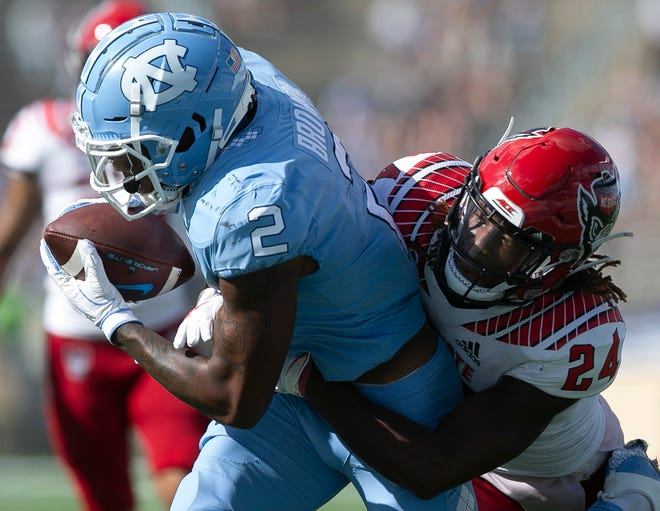 North Carolina's Dyami Brown (2) pulls in a 21-yard pass from quarterback Sam Howell ahead of N.C. State's Malik Dunlap (24) to set up a touchdown in the third quarter at Kenan Stadium on Saturday, October 24, 2020 in Chapel Hill, N.C.