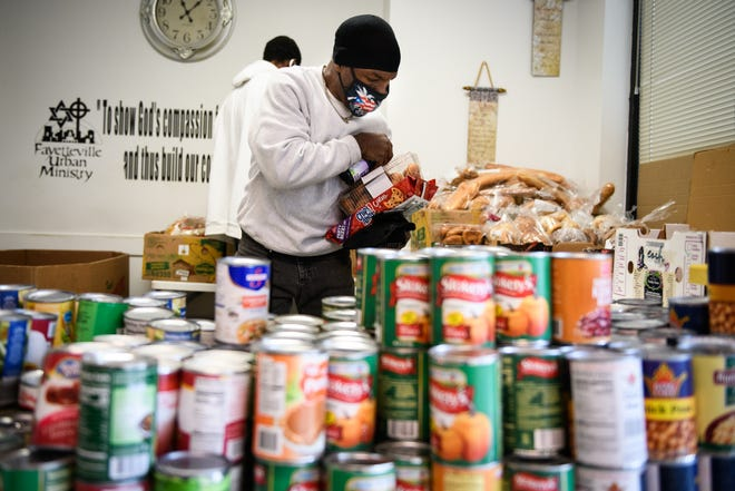 James Wright picks up food at Fayetteville Urban Ministry's food pantry on Oct. 26. Groups that operate the pantries say they have seen more people seeking help because of the pandemic.