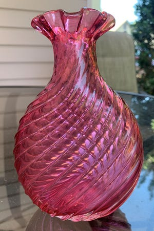 Cranberry art glass is made by adding gold to the molten glass, and then molded into the desired form, then reheated at a low temperature to achieve the cranberry color.