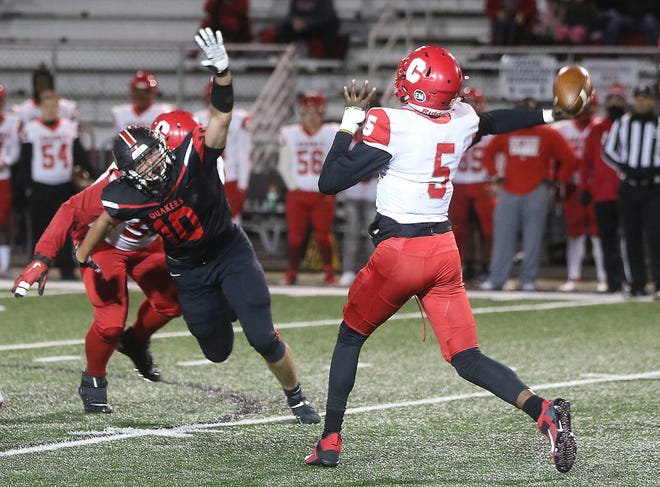 New Philadelphia's Mitchell Stokey pressures Youngstown quarterback Jason Hewlett in the first quarter of their Division III playoff game.