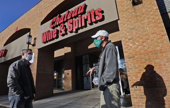Kirk Seman (left) talks to Mike Baker while they stand outside the Chateau Wine & Spirits liquor store in Dublin on Oct. 16.  Whenever a central Ohio liquor store gets a new delivery of bourbon, aficionados usually line up for a chance to purchase hard-to-find stock.