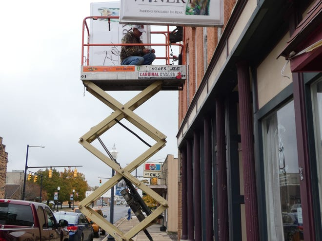 Ron Fox, owner of Fox Winery in Galion, repairs a sign in front of his Harding Way business on Monday. Fox said the pandemic is 'killing' his small business.