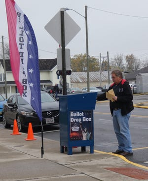 A man drops ballots into the ballot drop box outside the Crawford County Board of Elections office on North Walnut Street on Monday, Oct. 26, 2020.