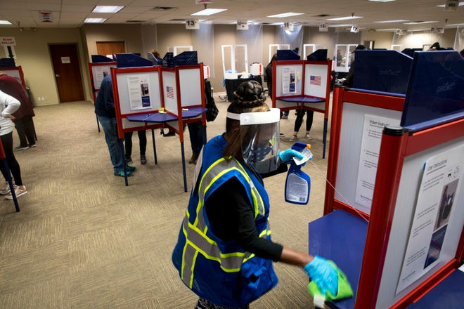 Tina Stephens cleans a voting space off after it was used at the Hamilton County Board of Elections early voting facility in Norwood on Monday, Oct. 26, 2020. Jeremy Jimmar, Hamilton County Board of Elections administrator, said that they had received about 48,000 early votes as of Monday morning and expected that they'd break 50,000 votes by the end of the day.