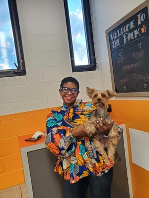 Erica Hill holds her 2-year-old Yorkshire Terrier dog, Kash, at Canine to Five day care. Hill has a demanding job and would not be able to do it and care for Kash without dog day care, she said.