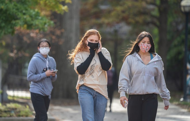 Masked University of Michigan students walk around campus in Ann Arbor on Tuesday, October 20, 2020 after Washtenaw County Health Department issued a Stay in Place order for University of Michigan undergrad students due to the rising number of COVID-19 cases on campus.